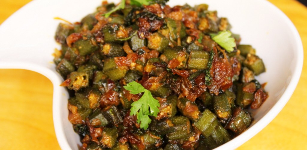 Stock photo of Bhindi (Indian okra). You can see in a cool shaped white bowl a bunch of sliced okra pieces with lots of spices and other veggies in there making it super tasty!