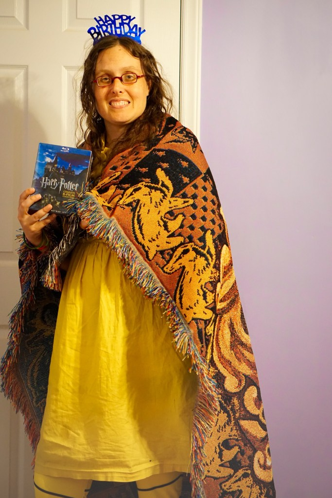 Veronica in her yellow dress with black and yellow Hufflepuff leggings, a Hufflepuff blanket around her shoulders, and the 8 movies in her hands.