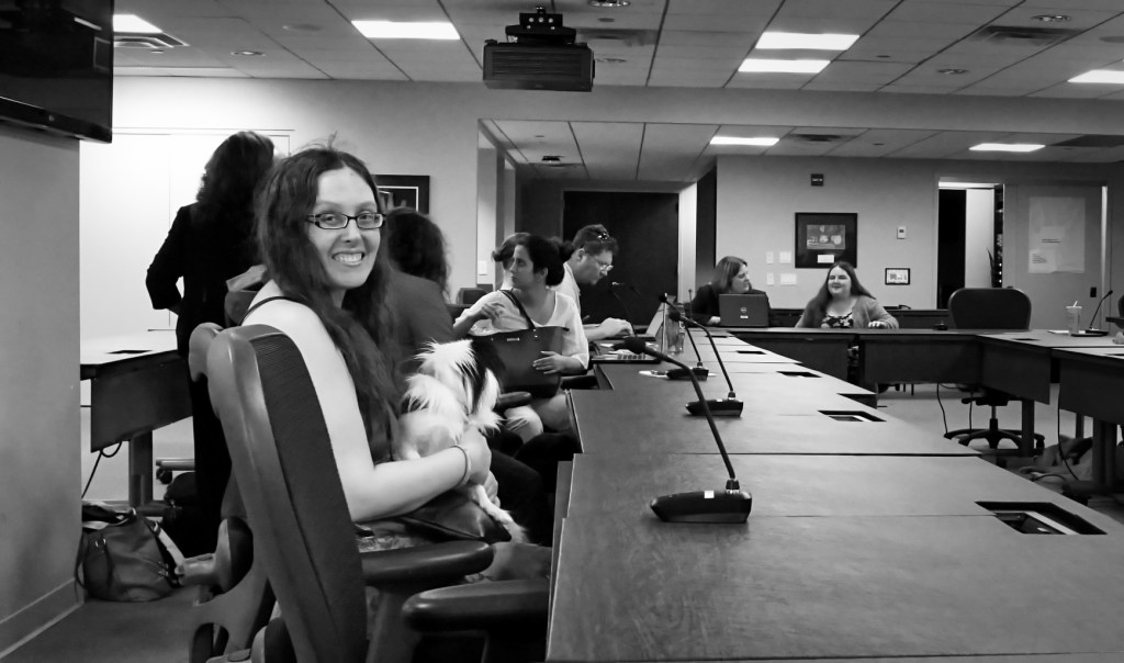 Veronica at the table with many other advocates, Hestia on her lap.