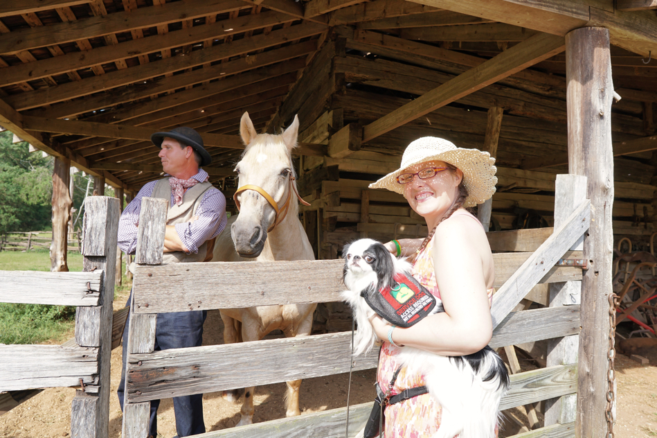 """Veronica and Hestia smile at the camera (well, I""""m guessing that's the face Hestia is making) with the horse and his caretaker in the background."""