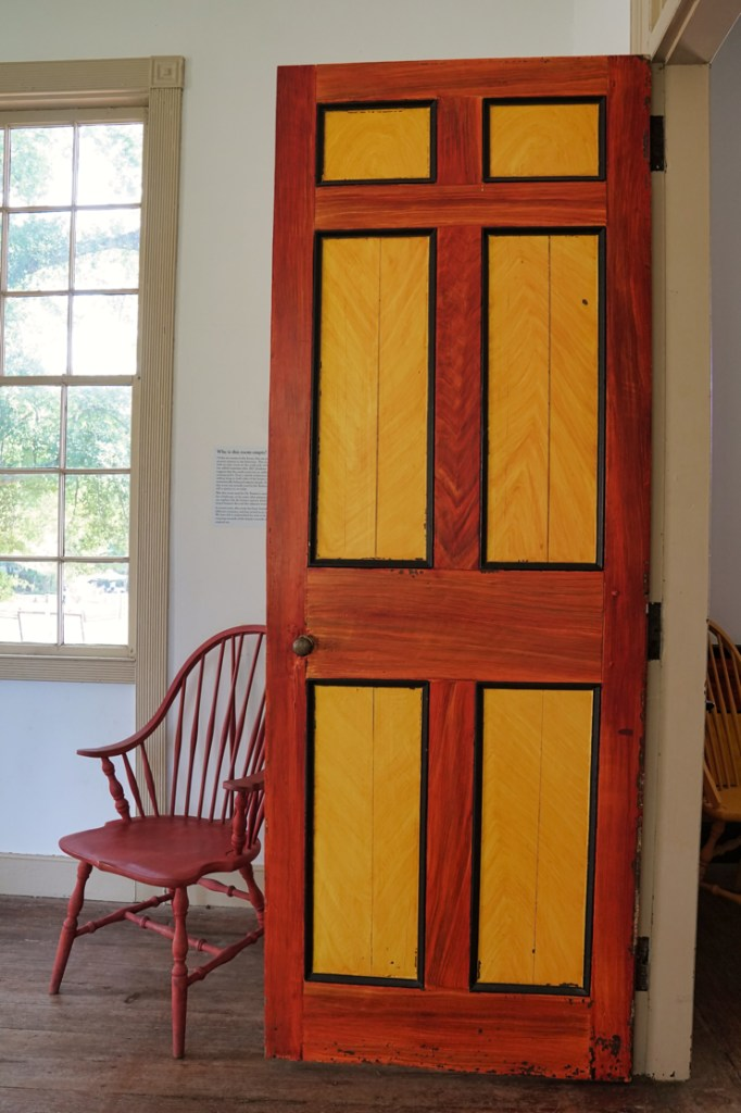 A pretty door in the main house.  It has yellow blocks on the inside, lines around the edges of these in black, and a red color on the other side of the black line.