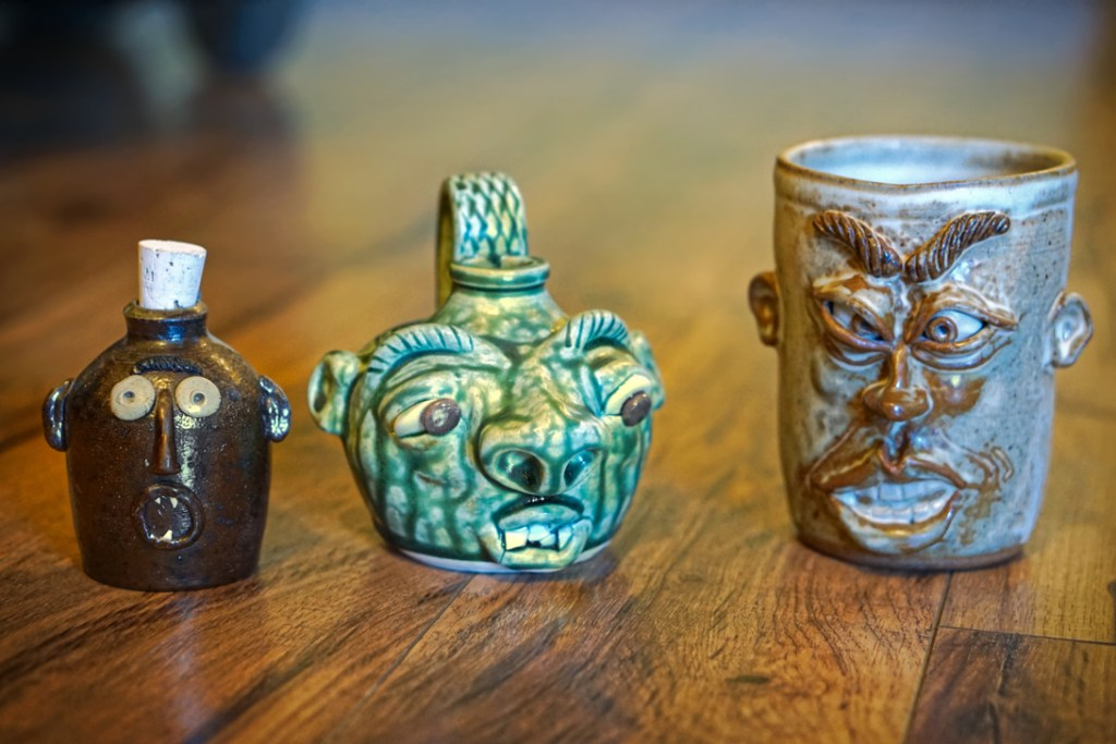 The face jugs!  From left to right a small brown face jug with an O for a mouth looking surprised.  The middle one is a slightly larger face jug of green tint that looks like a troll.  On the right is a face jug mug with a more intricate face with big heavy eyebrows.