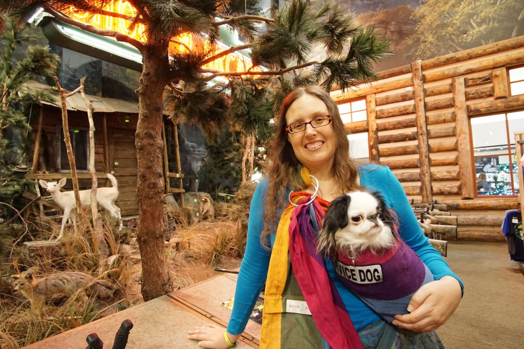 Veronica and Hestia in Bass Pro Shops.  Veronica is wearing a turquoise shirt, and Hestia is in her rainbow pouch with a big reflective service dog patch on it.