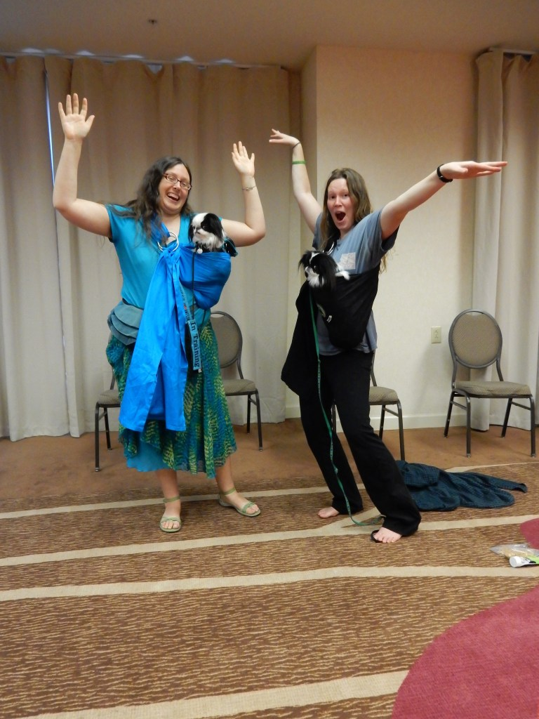 Veronica with Hestia and Lizzy with Kitten wearing the turquoise and black pouches respectively.  Veronica and Lizzy have their hands up in the air!
