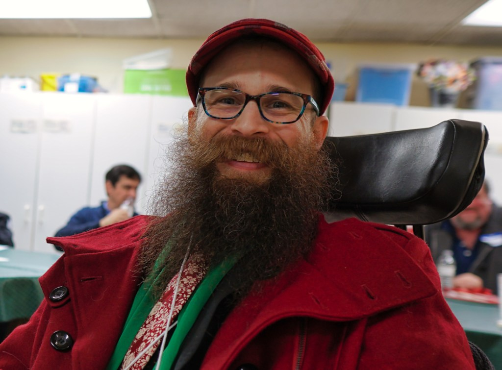 Brad with a red hat, red coat, green scarf, and red and white tie.