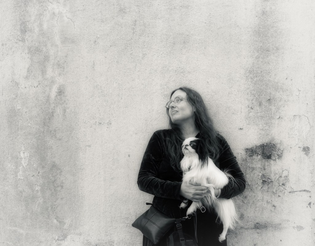 "A black and white picture of Veronica holding Hestia, both looking off into the distance with a look of hopeful expectation.  They are against a faded wall, and Brad describes this photo as ""cover art"" for an album."