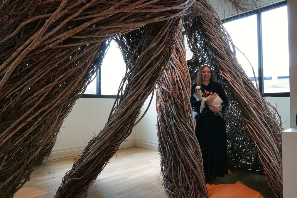 Veronica holds Hestia from inside a sculpture made of branches in a museum.