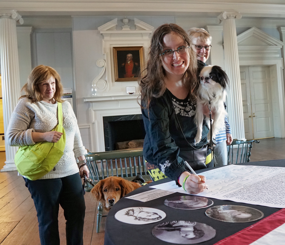 A giant copy of the Declaration of Independence is on the table, and Veronica is signing it.  She smiles as she holds Hestia.  Jenine and Roger are behind Veronica and Hestia looking on.