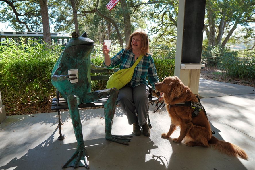 Jenine and Roger share a cup of tea with a big bronze frog on a bench