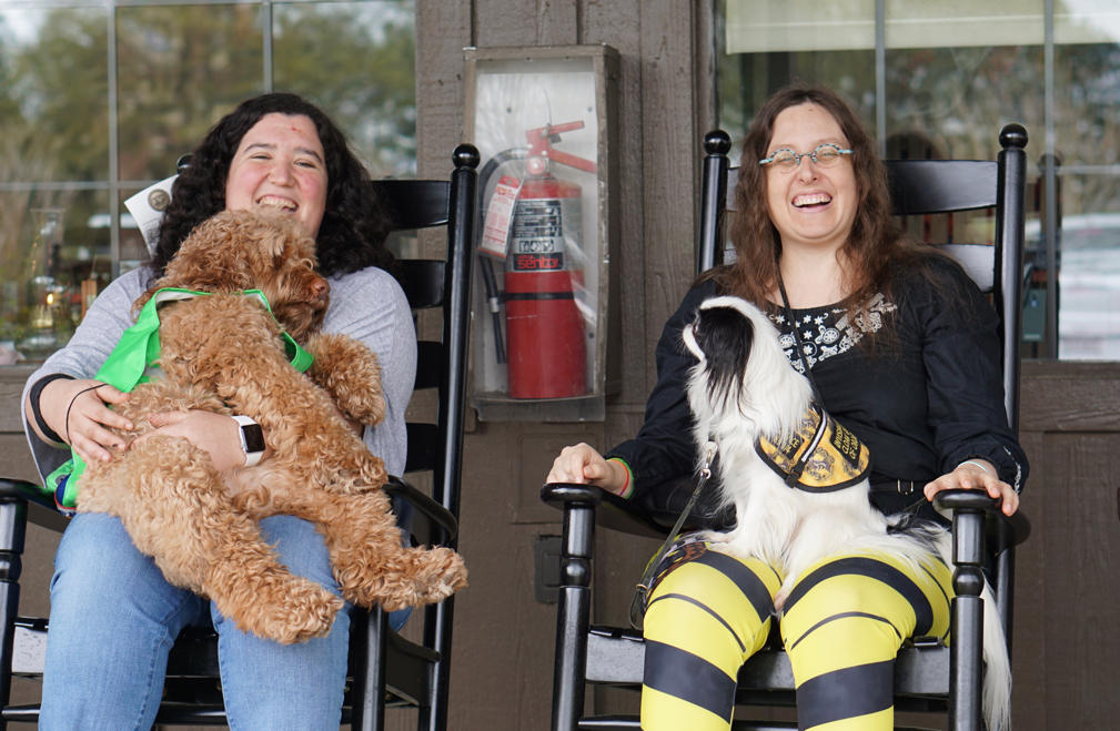 Hanna wearing a grey shirt with 40 lb doodle Sasha on her lap.  Sasha is wearing a green ruffwear coat.  Veronica wearing Hufflepuff leggings and a black shirt with Hestia wearing a Hufflepuff vest.  They are sitting on rocking chairs outside Cracker Barrel.