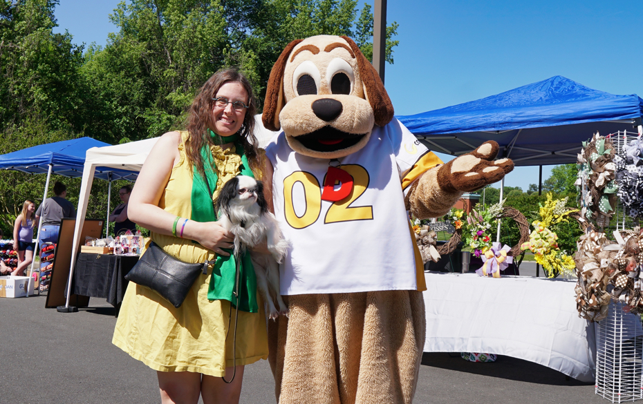 """Veronica and Hestia with a person dressed up as """"Diggity Dog"""" in a dog costume."""