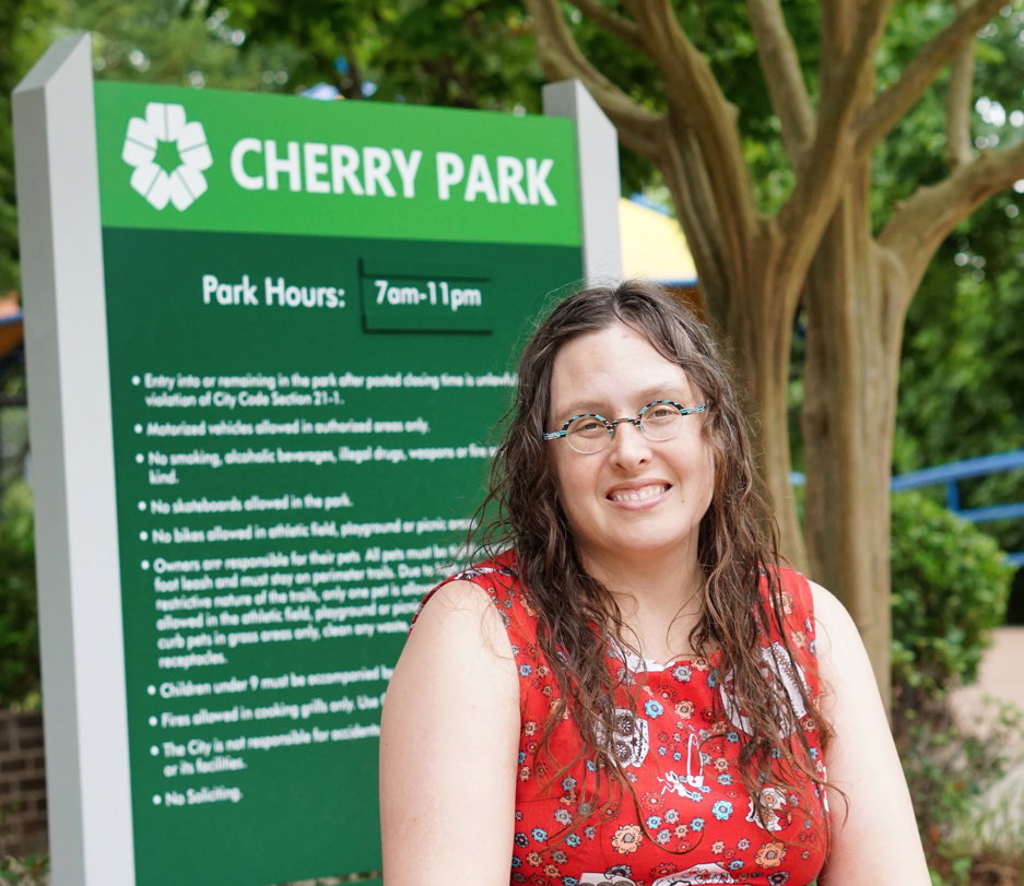 Veronica sits in front of a Cherry Park sign, her hair still wet.