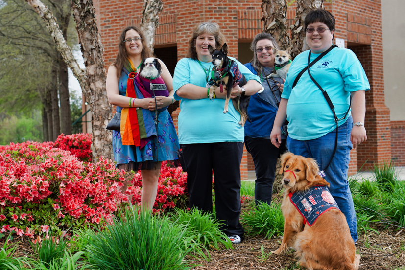 """Veronica, wearing her blue butterfly dress, carries Hestia in a rainbow pouch with a patch saying """"service dog"""".  Next to her stands Deanna, wearing a turquoise shirt, with Max.  Next to her stands Tami, a woman wearing a blue shirt, carrying her service dog, a chihuahua named Chili wearing a green bandana.  On the far right stands Allison, wearing the same shirt as Deanna, and her Golden Retriever Ruby, who wears a blue heartbeat vest."""