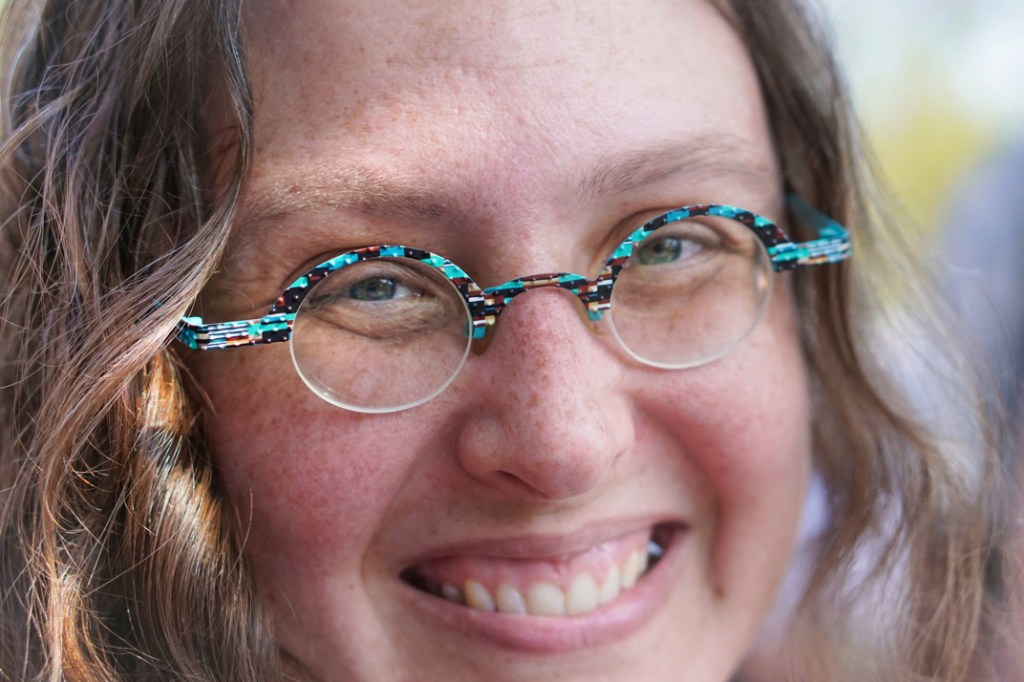 A closeup of my face, you can see my round glasses that are predominantly turquoise with some other colors thrown in.