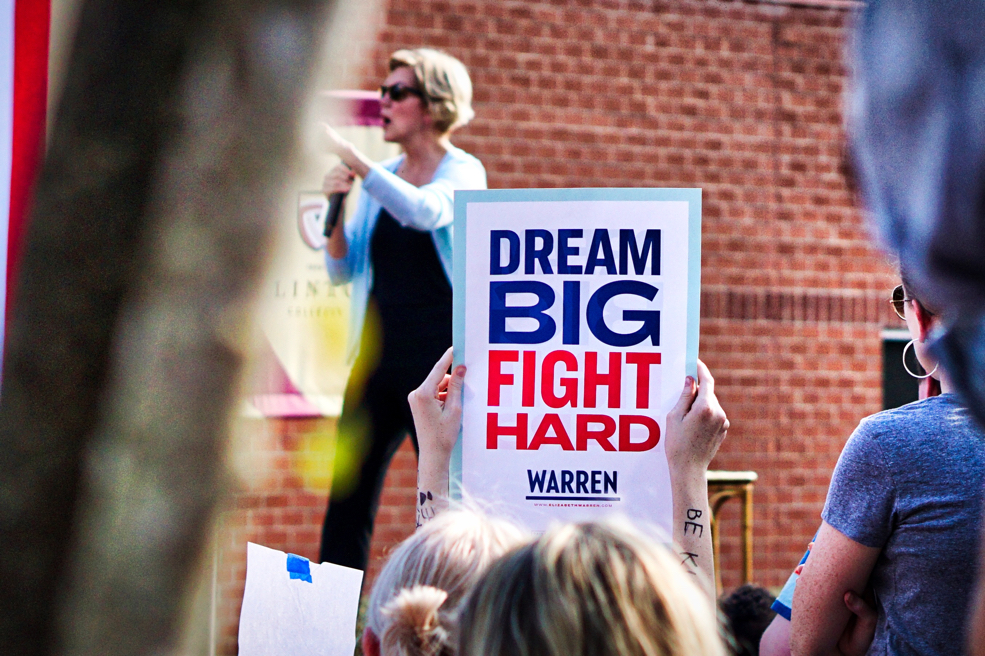 """Elizabeth Warren gestures in the background.  In the foreground someone holds up a sign that reads """"Dream big, fight hard""""."""