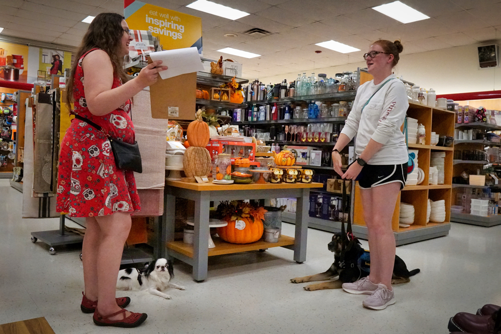 Kilo and Hestia lie on the floor in TJ Maxx as Veronica and Cynthia discuss the Manners Evaluation in front of a pumpkin themed display.