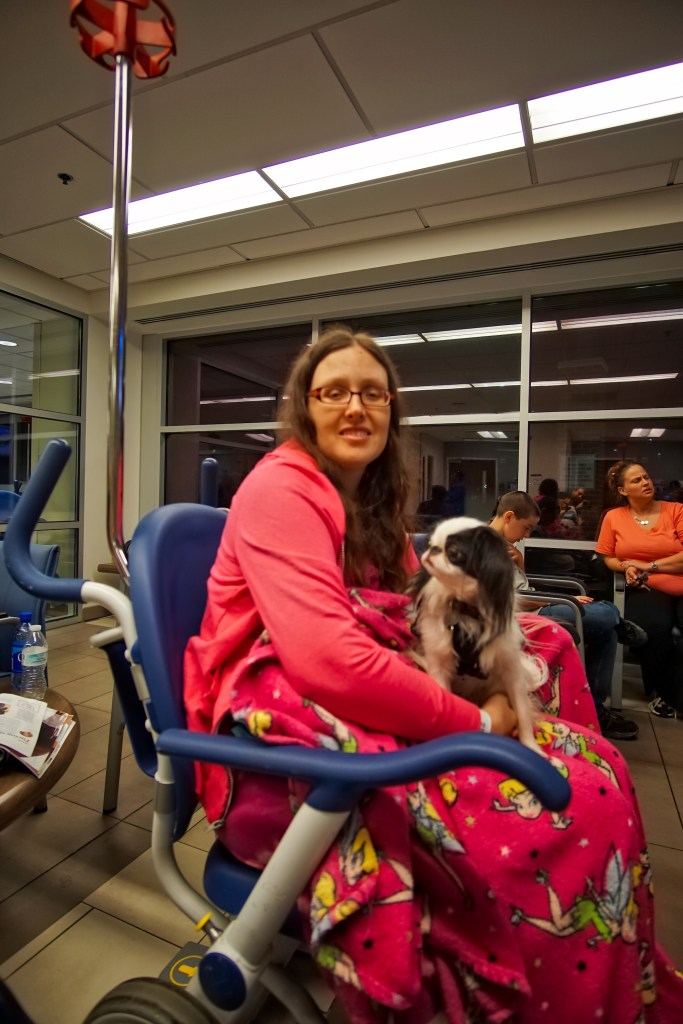 Veronica in the emergency room in an ER wheelchair, with Hestia on her lap.