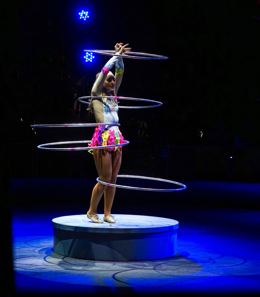 A woman in a brightly colored costume has five hula hoops spread out over her body.