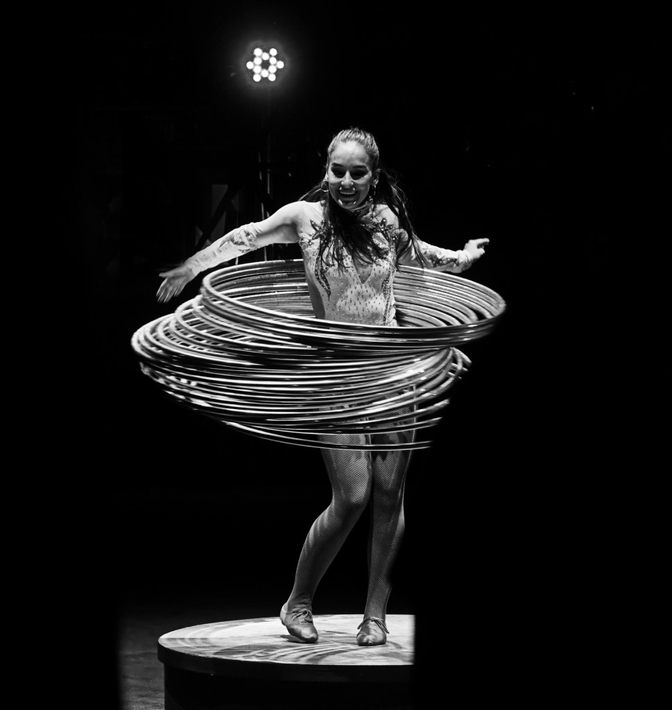 Black and white picture of the woman with like 30 hula hoops all around her waist swinging.