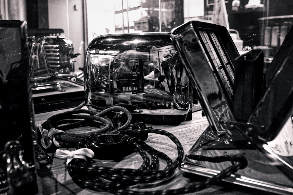 A black and white picture of many chrome toasters, with lots of interesting things reflecting in their surfaces.