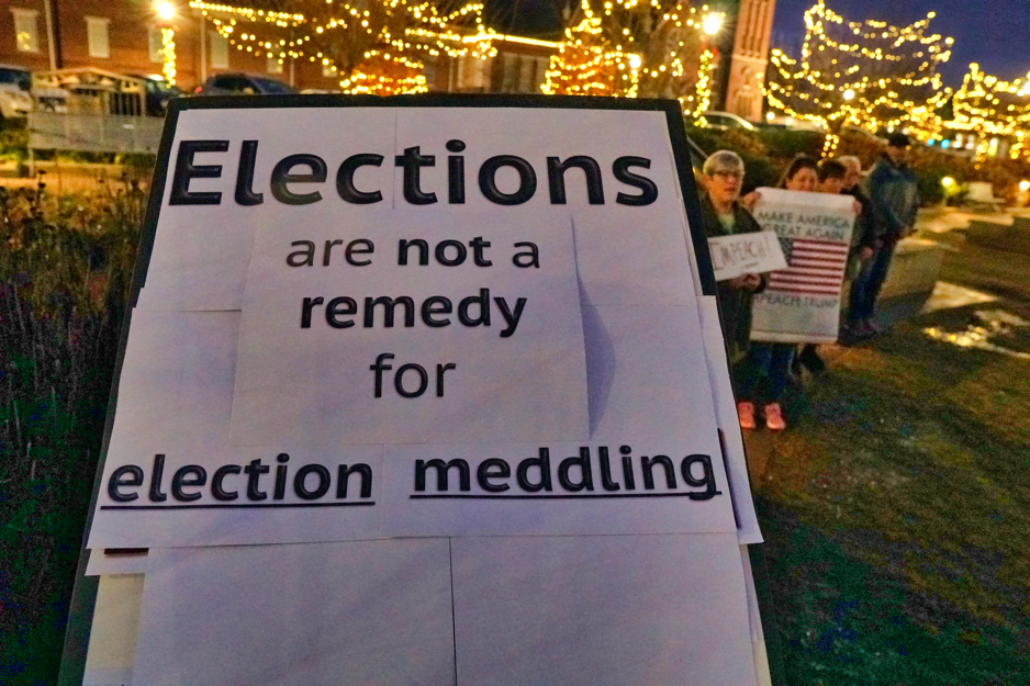 """The front of Brad's sign says """"Elections are not a remedy for election meddling""""."""