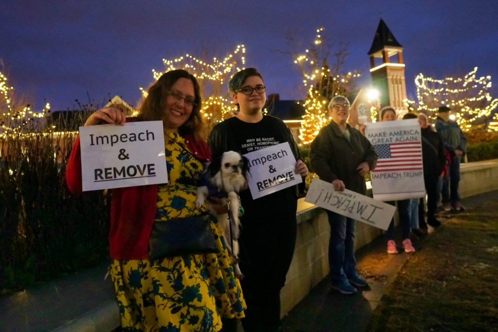 """Veronica in a yellow dress with blue leaves and a red sweater holds up a sign reading """"Impeach and remove"""".  She is holding a small white and black dog with a smushed nose.  Scarlet is wearing black and stands next to Veronica and Hestia, holding another """"Impeach and remove"""" sign."""