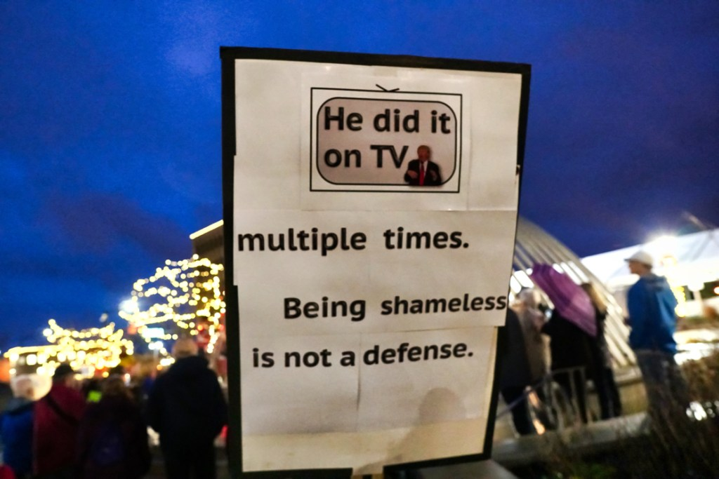 """The back of Brad's sign says """"He did it on TV multiple times.  Being shameless is not a defense."""""""