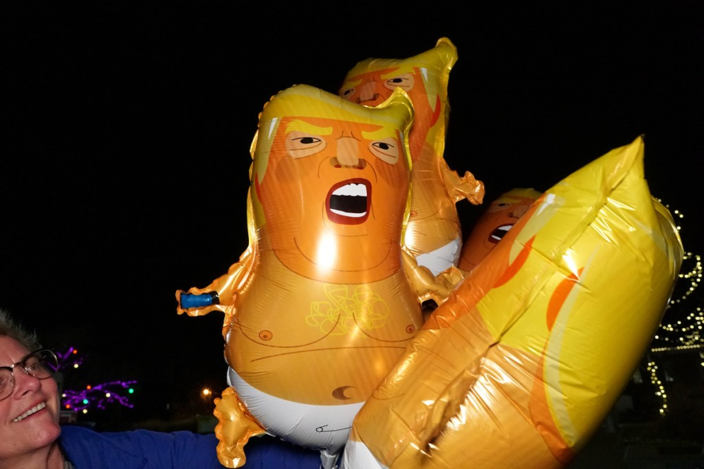 Balloons of Donald Trump in a diaper holding a cell phone in his hand!