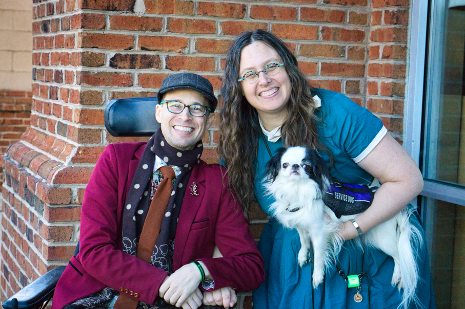 Brad, a man in a power chair wearing a merlot blazer, rust tie, brown scarf, and brown newsboy hat, sits in front of a brick wall.  Veronica leans over next to him, smiling and holding Hestia, who is also looking at the camera.