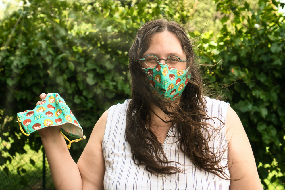The wind blows Veronica's long brown curly hair as she models a teal mask with cartoon faces of Harry Potter characters on it, holding a matching one for Brad in her hand.