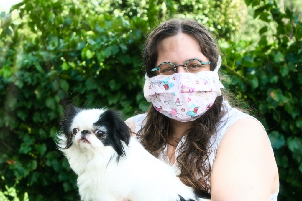 Holding Hestia, a small white and black dog, Veronica models a pink mask with pastel colored dogs on it.