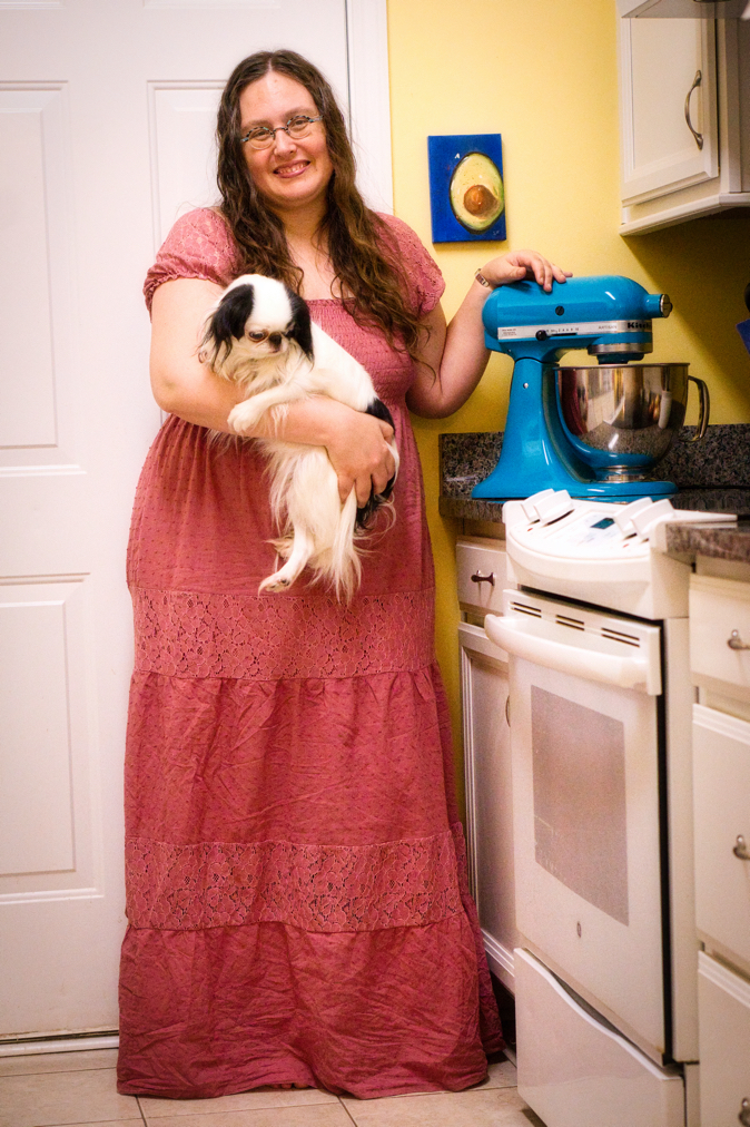 Shot from waist height, a smiling white woman holds a small white and black dog and rests her hand on a dark teal mixer on a kitchen counter. Her light mauve, floor-length dress has lacy sleeves and lace overlays in two wide horizontal stripes under the waist.  The dog looks downward forlornly as it wraps its from leg across the woman's arm.