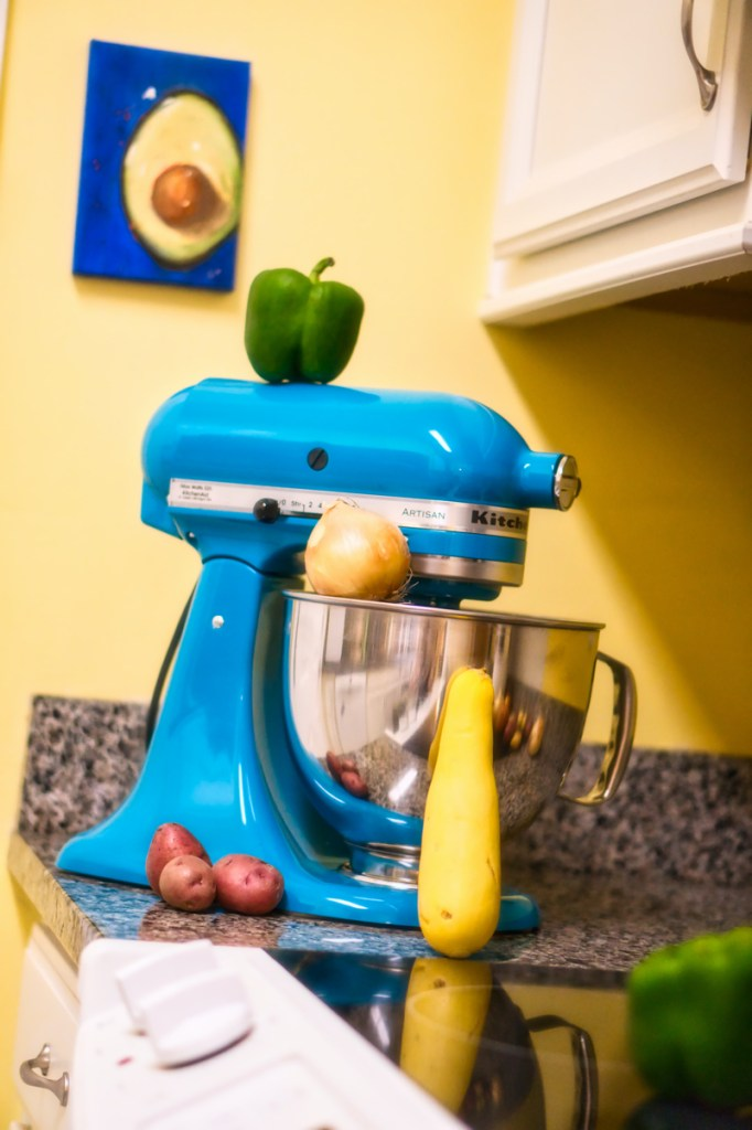 Closeup of a dark teal Kitchenaid mixer on a gray granite countertop in front of a yellow wall. There's a blurry green bell pepper on the glass stovetop in the foreground and one on top of the mixer, an onion resting on the top of the bowl, a yellow squash leaning up against the bowl from the counter, and three tiny red potatoes clustered at the base of the mixer.