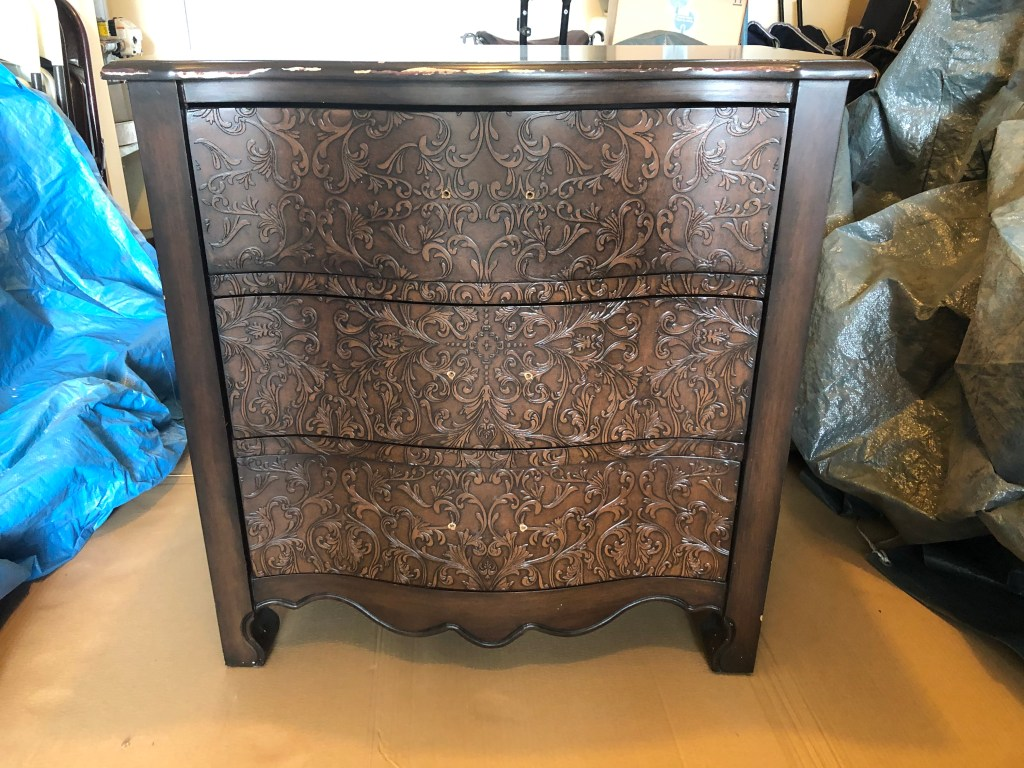 This is the dresser before paint.  It is about 3 feet tall by three feet wide with three drawers.  The front is carved intricately with an exotic pattern.  The middle front of the dresser bulges out in a curved manner.  In this picture, I already removed the handles for painting.
