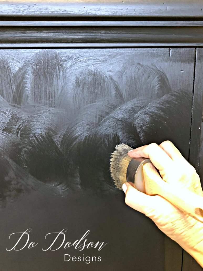 Applying DIY black wax to a distressed dresser.