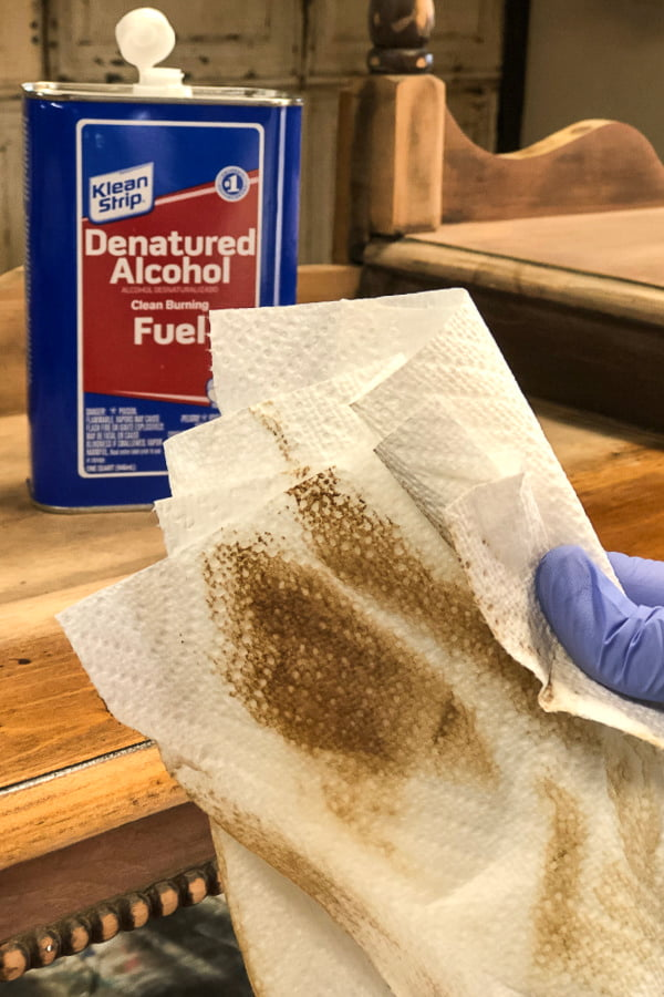 Denatured alcohol was used to remove the leftover dust from sanding down to the barewood. It cleans and evaporates quickly so that I can move to the next step in creating a raw wood furniture finish on this old piece.