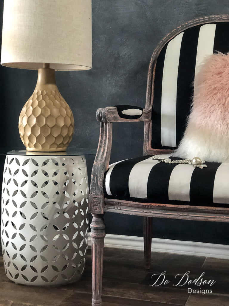 I love how the bold black and white stripes complement the aged finish on the vintage armchair.