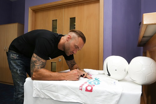 Calum Best signs some PDSA merchandise before the game
