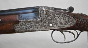 MERKEL 203E LUXUS - 20 GAUGE - DOUBLE TRIGGERS - DEEP GAME SCENE ENGRAVED WITH OAK LEAF CARVED STOCK - OAK AND LEATHER CASE
