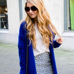 Elien Migalski of Dogs and Dresses is wearing a bright blue cardigan and grey blouse by VILA, patterned skirt from Sienna & Lois.