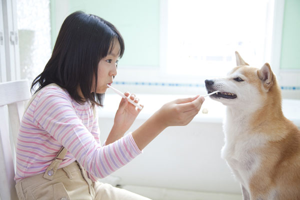 A woman brushing her teeth with her dog.