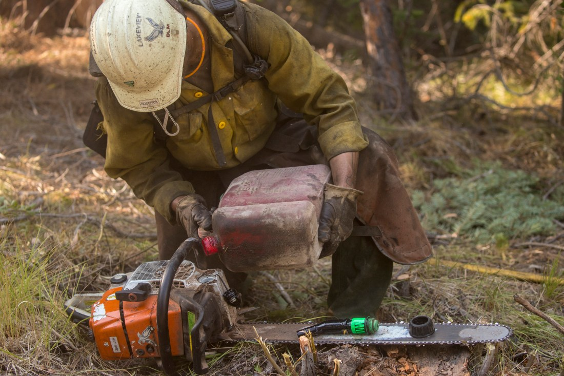 Firefighter maintains a chainsaw.