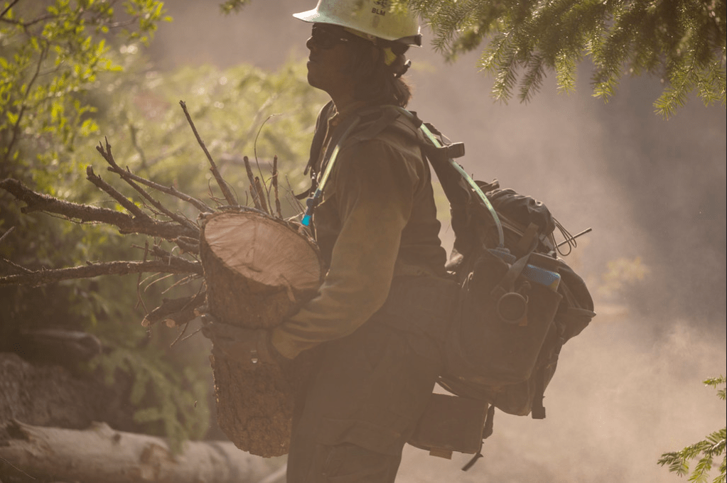 Firefighter clears debris at the Cougar Creek Fire.