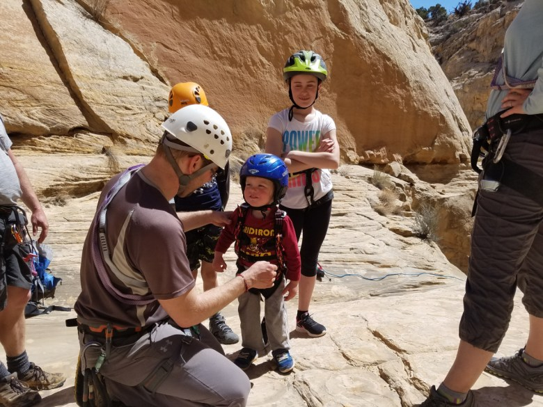 A man helps a little boy put on a climbing harness while other kids look on while standing next to a rock wall.