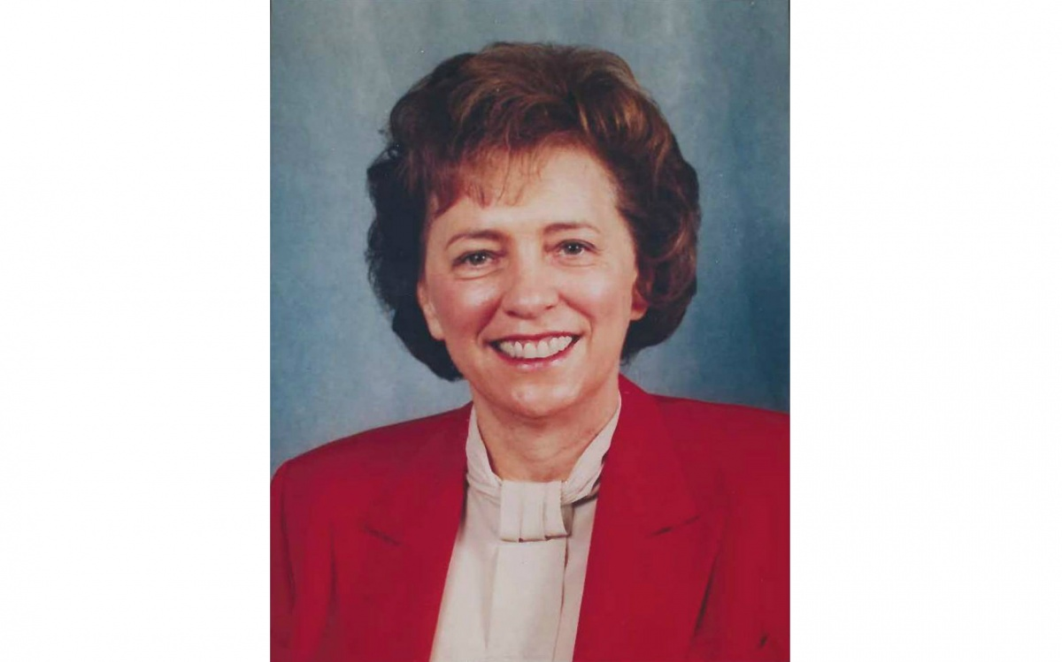 A head shot of a woman, Kathy Karpan, against a blue background. She is smiling and wearing a white blouse and a red blazer.