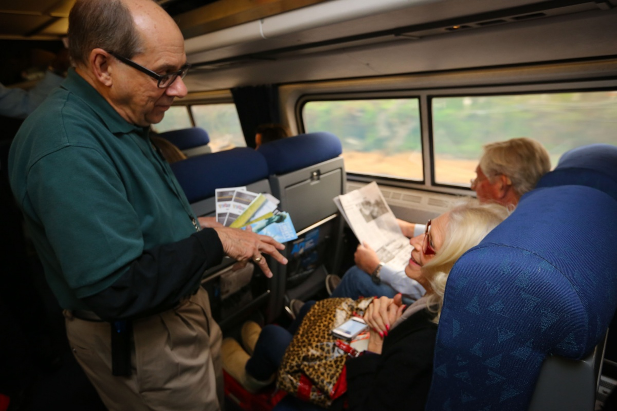 A volunteer wearing a green shirt passes out pamphlets to two seated passengers.