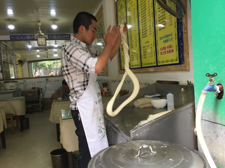 Making noodles at a street side shop.