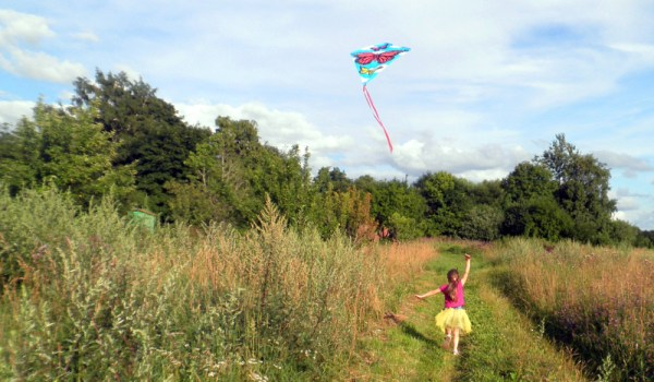 A girl flying a kite in the countryside on a summer day (CC BY-SA 4.0 by Wikimedia user)