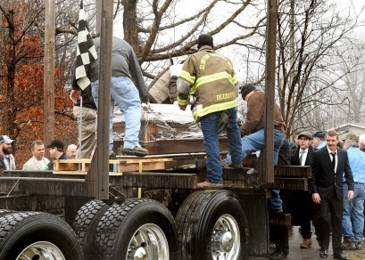 Okey Dalton body is placed on logging truck driven by son Darrin Dalton.