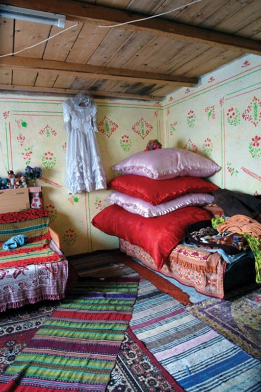 Veresti, Romania. This is not a wealthy Roma home but the family earned enough to have the interior decorated instead of carpets hanging on the walls